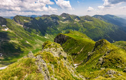 Valley in romanian mountains view from the edge above. Gorgeous summer landscape in fine weather with cloudy sky Stock Photos