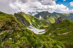 Valley in romanian mountains view from the edge above. Gorgeous summer landscape in fine weather with cloudy sky Royalty Free Stock Photo