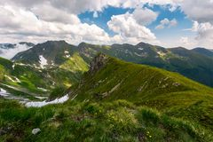 Valley with snow in summer mountains. Gorgeous mountainous landscape of Carpathians. rocky cliffs and grassy hillsides under a cloudy sky. Fagaras ridge of Royalty Free Stock Photo