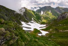 Valley with snow in summer mountains. Gorgeous mountainous landscape of Carpathians. rocky cliffs and grassy hillsides under a cloudy sky. Fagaras ridge of Royalty Free Stock Image