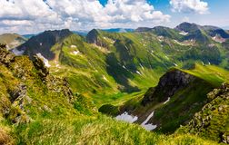 Valley with snow in summer mountains. Gorgeous mountainous landscape of Carpathians. rocky cliffs and grassy hillsides under a cloudy sky. Fagaras ridge of Royalty Free Stock Photos