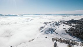 Valley on top of the mountain covered with snow over clouds on a sunny day photographed from the air royalty free stock image