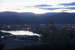 Valley Town by River and Mountains at Night Stock Photography