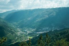 Valley of Zezere River with small village underneath. The long wooded valley of Zezere River with de Manteigas village underneath, in a sunny day at Serra da stock photography