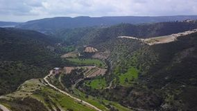 Valleys in mountains in Cyprus in spring day, aerial view. Bright greenery stock video footage