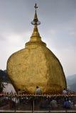 Vallfärdar att be, och klistra guld- folier på guld- vagga tillsammans på den Kyaiktiyo pagoden, Myanmar med rad av små klockor Arkivfoto