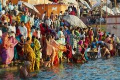 Vallfärdar bad i heliga Ganges River på soluppgång i Varanasi, Indien royaltyfri bild