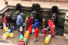 Vallfärdar mot efterkrav sakralt vatten från springbrunnen i den Katmandu Durbar fyrkanten, Nepal Royaltyfri Bild