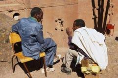 Vallfärdar samtal med den monolitiska vagga-högg ut kyrkan på bakgrunden i Lalibela, Etiopien Fotografering för Bildbyråer