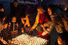 Vallfärdar tända upp stearinljus på den Boudhanath stupaen Royaltyfri Foto