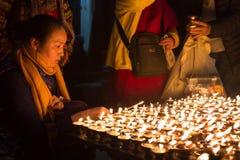 Vallfärdar tända upp stearinljus på den Boudhanath stupaen Arkivfoton