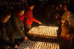 Vallfärdar tända upp stearinljus på den Boudhanath stupaen Arkivfoto