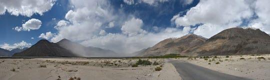 Valli dell'alta montagna: ampio deserto, nelle catene montuose di distanza, nella priorità alta una striscia della strada che con Fotografia Stock Libera da Diritti