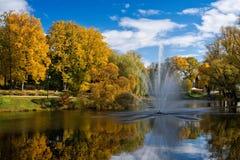 valmiera latvia Paisaje del otoño de la ciudad con una charca y una fuente fotos de archivo