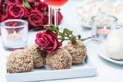 Valnöt-choklad tårtor, blommor och rosa wine Arkivbilder