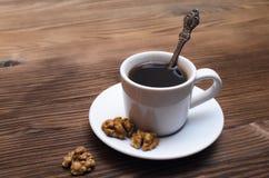 Valnöt och varm kaffekopp royaltyfria foton