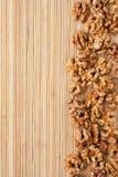 Valnöt som ligger på en matt bambu Arkivfoto