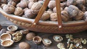 Valnötter i en korg på en träbakgrund arkivfilmer