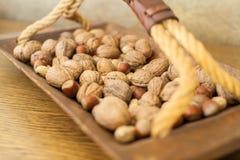 Valnötter och jordnötter i träbunke med handtaget royaltyfri fotografi
