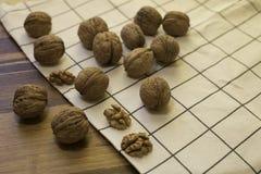 Valnötter och kärnor av valnöten på den lantliga trätabellen som täckas med kökshandduken Bekläda beskådar Arkivfoton
