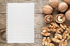 Valnötter och papper för recept Royaltyfri Foto