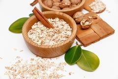 Valnötter och rullande havre i träplattorna med pinnar av kanel, träservice, sked, gröna sidor, sund ny organisk mat Royaltyfri Fotografi