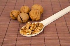 Valnötter på en brun träbakgrund med träskeden Royaltyfri Bild