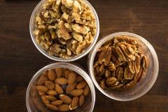 Valnötter, pecannötter och mandlar i behållare Fotografering för Bildbyråer