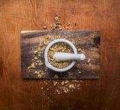 Valnötter som krossas i en mortel på slut för bästa sikt för skärbrädaträlantligt bakgrund upp royaltyfri foto