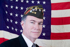 Valor and Respect. A man in a veteran of foreign wars cap standing in front of a forty-eight star US flag Stock Images