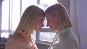 Valores da mãe, mum feliz com a filha a aconchegar-se um com o otro acima das cabeças em retroiluminado na sala contra a janela