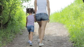 Valores familiares Control joven de la madre la muchacha del pequeño niño de la mano del paseo en parque back metrajes