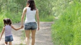 Valores familiares Control joven de la madre la muchacha del pequeño niño de la mano del paseo en parque back almacen de metraje de vídeo