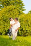 Valores familiares Familia caucásica feliz de padre y de hijo que llevan a cuestas al aire libre Imágenes de archivo libres de regalías