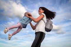 Valores familiares: A mamã com óculos de sol gerencie com uma filha pequena em um vestido azul contra o céu e as nuvens authentic fotografia de stock royalty free