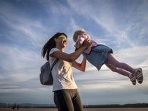 Valores familiares: A mamã com óculos de sol gerencie com uma filha pequena em um vestido azul contra o céu e as nuvens authentic fotos de stock royalty free