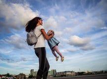 Valores familiares: A mamã com óculos de sol gerencie com uma filha pequena em um vestido azul contra o céu e as nuvens authentic foto de stock royalty free