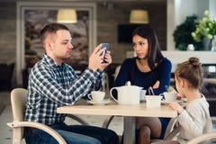 Valores familiares modernos El padre envició sobre usar la PC de la tableta de los dispositivos electrónicos, mientras que su esp Imagenes de archivo