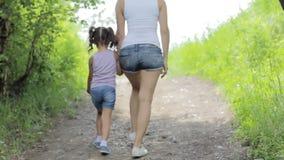 Valori familiari Giovane tenuta della madre la ragazza del piccolo bambino della mano sulla passeggiata in parco back stock footage