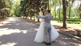 Vals nuevamente casado romántico del baile de la pareja en el parque en su día de boda almacen de video