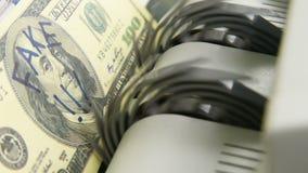 Vals ons dollarrekening onder echt geld in een tellende machine stock videobeelden