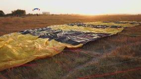 Valscherm die op de grond in de zonsondergangstralen liggen van de zon op het vliegveld stock video