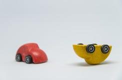 Valt den röda kraschade gula leksakbilen för leksaken bilen med vit backgrond och den selektiva fokusen Royaltyfri Foto