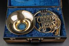 Valthorn i ett gammalt fall på en trätabell Härligt polerat musikinstrument fotografering för bildbyråer