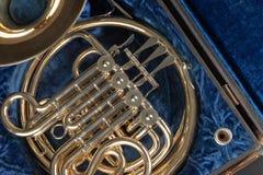 Valthorn i ett gammalt fall på en trätabell Härligt polerat musikinstrument arkivfoto