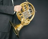 Valthornspelare Horn för musikinstrument i händerna av mannen för hornist A i en dräkt med ett musikinstrument royaltyfri bild