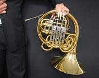 Valthornspelare Horn för musikinstrument i händerna av mannen för hornist A i en dräkt med ett musikinstrument arkivbild