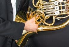 Valthornspelare Horn för musikinstrument i händerna av mannen för hornist A i en dräkt med ett musikinstrument fotografering för bildbyråer