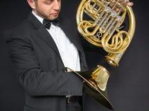 Valthornspelare Horn för musikinstrument i händerna av mannen för hornist A i en dräkt och i en fjäril med ett musikinstrument royaltyfri fotografi