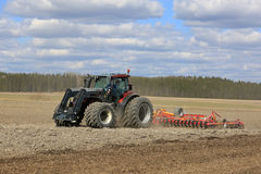 Valtratractor en Landbouwer op Gebied bij de Lente Stock Afbeeldingen